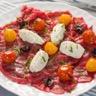 Carpaccio de bœuf tomates confites olives noires au Tartare ail et fines herbes