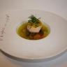 Médaillon de saumon en vapeur d'agrumes et aneth sur un bouillon de légumes printaniers safrané