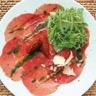 Salade de roquette sur carpaccio de boeuf au pesto huile d'olive aux piments et copeaux de parm...